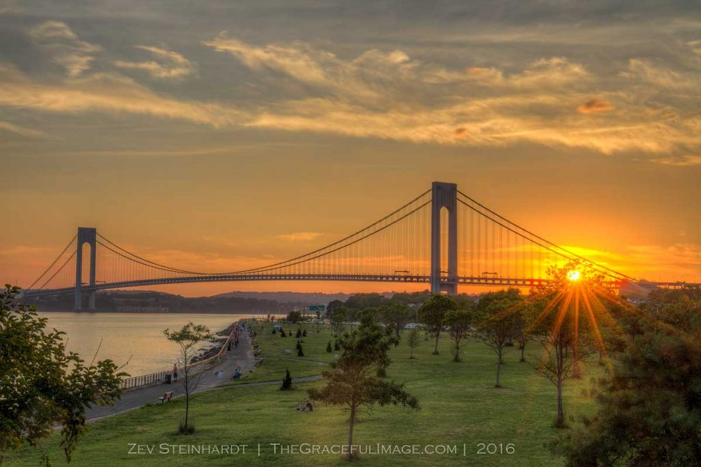 The Verrazano-Narrows Bridge at sunset in July, with Shore Park in the foreground.